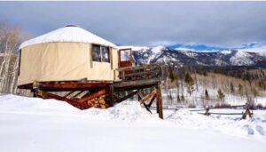 Yurt and snow capped mountains at Never Summer Nordic